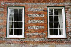 Pair of windows in flint wall with brick quoins