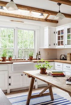 trestle table in middle of kitchen - exposed beams - white kitchen