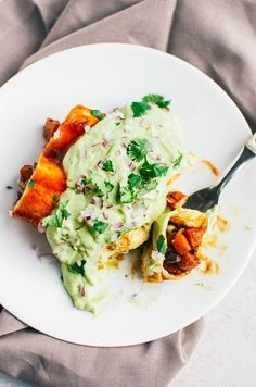 Chipotle Sweet Potato & Black Bean Enchiladas - These spicy enchiladas do not skimp on flavor, and just to be sure they are smothered in a delicious avocado cream. (Vegan & GF) | RECIPE at