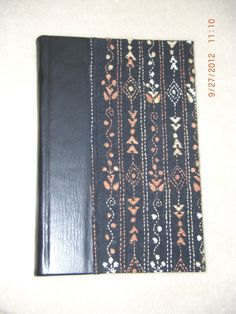 Blank journal. Black leather spine with embroidered cloth cover. Made by Roxanne