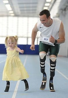 Olympic athlete Oscar Pistorius runs with 5-year-old Ellie May Challis. Photographed by Andy Hooper.