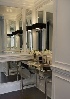 Stunning powder room with white wainscotting, chrome sink and black shaded sconces.