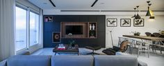 Architect and designer Roy David was tasked with renovating a 1,184-square-foot apartment located in a luxury tower in Tel Aviv. The remodeled living room features a Gus* Modern sofa and an Eames lounge chair.