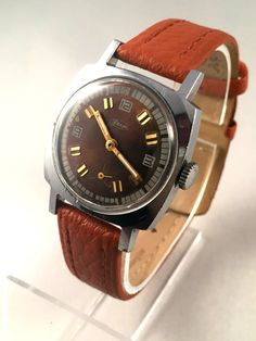 """This is a vintage watch ZIM- VICTORY ( """"Pobeda"""") made in USSR. This watch is in a fully working order. Mechanical movement, manual winding. Gorgeous brown dial and gold numerals on it.  Year: 70s  Dial diameter: 30mm ( a bit smaller than average mens size watch)    Cosmetic Condition: Good with some obvious signs of use.    Brand new quality genuine leather wristband included.    """"Pobeda""""(""""Victory"""") watches were made by the First Moscow watch factory, Kirov following the Second World War in…"""
