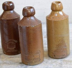 Three antique stoneware ginger beer bottles, London interest