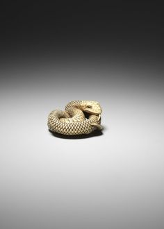 Netsuke. Coiled snake. Made of ivory, eyes inalid. Made by: Okatomo 岡友. Edo Period t Date: late 18thC. Made in: Kyoto-shi (Asia, Japan, Kyoto-fu, Kyoto-shi) Materials: ivory. Technique: carved. British Museum number: 1945,1017.603
