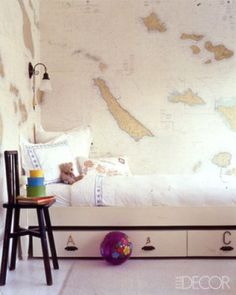 Captain Kid ~ In an actress's Malibu beach house, interior designer Kerry Joyce gave one of the children's rooms a high-seas look by wallpapering it with sea charts; the sconce and chair are by Omega Too.