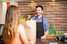 Male cashier being friendly to a customer stock photo
