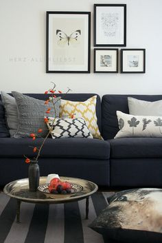Dark sofa with pops of autumn orange. Shimmery floor pillow. Textured couch pillows. Naturalist wall art. <3
