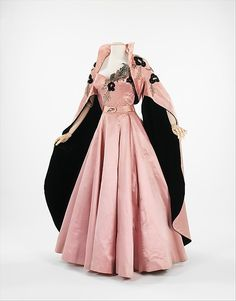 Evening ensemble ~ front view of a gown by Italian designer, Micol Fontana (1943), The pink silk satin dress is full skirted & strapless, with a sweetheart neckline, and lavish embroidered & beaded decoration along the decolletage, down the front of the bodice.  The bollero jacket has a stand up collar & huge cascading bell sleeve, which fan open at the elbow, revealing the black silk lining.