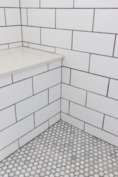 Master bathroom shower. Subway tile with grey grout, stone bench and penny round tiles for the shower floor. Clean, classic, simple design for a master bathroom: