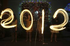 "Women use sparklers to draw ""2012"" for photographers, in front of a house, as they celebrate New Years Eve in Manila December 31, 2011. REUTERS/Romeo Ranoco  (PHILIPPINES"