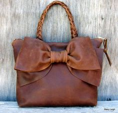 The bag has a large bow on the front. Feminine but in rustic leather its not prissy. Rocky Mountain Distress hide is a pull up leather, so it lightens