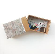 """Πρωτότυπη Ευχετήρια Κάρτα σε Κουτί σε σχήμα Σπιρτόκουτου !! Η διάστασή του είναι 7,6 x 12,3 x 4,9 cm.Έχει τυπωμένα γράμματα Bon Voyage! Το πάνω μέρος έχει ντυθεί με print χαρτί με vintage χάρτη και έχει λευκή ζικ ζακ κορδέλα.Εχει μικρά χάρτινα διακοσμητικά με θέμα το ταξίδι!Αεροπλάνο ,διαβατήριο, βαλίτσες και σακ βουαγιάζ.Ωραία ιδέα για να αποχαιρετήσεις κάποιον δικό σου άνθρωπο που πάει""""στα ξένα """"για δουλειά ,για σπουδές κτλ.  Μπορείς να προσθέσεις το μήνυμά σου με τις ευχές σου. Box, Cards, Decor, Bon Voyage, Snare Drum, Decoration, Maps, Decorating, Playing Cards"""