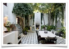 a bbq, a fountain, a fireplace, gorgeous tiling and great trees and plants - the perfect outdoor space