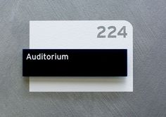Overlaid black label on white with cut-out room number. Room and environmental sinage