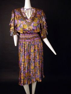 1980s dress in a poly satin with a floral and geometric print. the colors are yellow, orange, purple, black and aqua. V-neckline with a string tie and bead ends at the neck. Balloon sleeves with bias