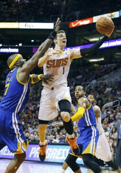 Phoenix Suns' Goran Dragic (1), of Slovenia, drives past Golden State Warriors' Jermaine O'Neal (7) to score as Warriors' Andre Iguodala, right, stands near during the second half of an NBA basketball game Saturday, Feb. 8, 2014, in Phoenix. The Suns won 122-109. (AP Photo/Ross D. Franklin)