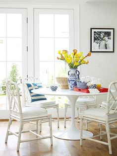 Classic white rattan chairs meet a modern tulip table for pretty summer house dining style