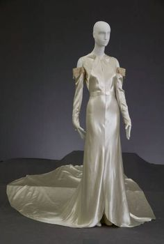 "Wedding Dress, Madame Marguerite, Chicago: 1934, bias-cut silk satin, lace, rhinestones, pearls. ""With the dawn of Hollywood's golden age, glamour started to influence wedding fashion, and the long sweeping satin trains worn by movie stars quickly became the fantasy of every bride. The way in which the fabric is cut for these dresses is called bias. By cutting fabric on the bias (cross-grain), it stretches around the form. This cut gained popularity in the 1930s...and remains fashionable…"
