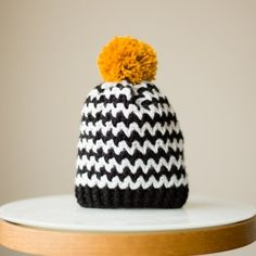 Crochet this striking black and white beanie with a mustard pom pom!  Simple free pattern via Kat Goldin with 6 different sizes available!