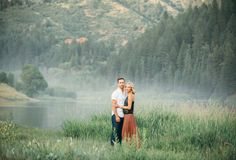 Engagement photos by the lake with fog and pine trees. Casual engagement photos. gideonphoto.com