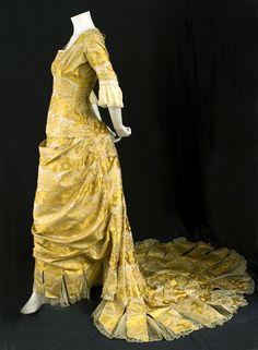 Satin damask bustle gown with provenance, c.1876    Bustle gowns make a dramatic statement. The gown is from the first bustle period, generally thought to be the most graceful. While the eye is drawn to the back of the draped skirt, the silhouette does not have the centaur shape of the 1880s.