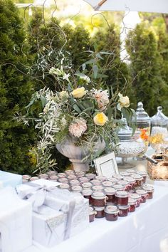 A rustic floral arrangement with wiry branches accents the wedding favors and gift table. Janae Shields Photography.