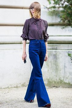 A polka dot bow-tie blouse is worn with high-waisted jeans, glasses, and platforms