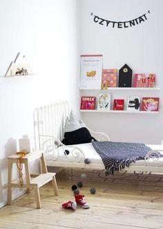 Bois clair et petit lit en fer forgé pour la chambre d'enfant.