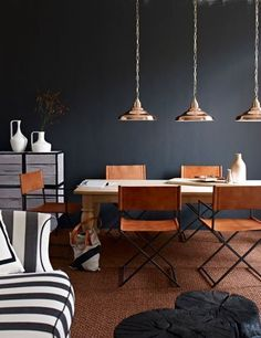 These barely-there metal and leather chairs pop against the black wall of this dining room. via Babble