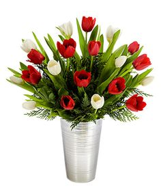 This celebration of the magnificence of tulips will make someone joyful! Red and white tulips comprise this bold, brilliant and beautiful arrangement with a silver metallic lined ceramic vase making it all come together.