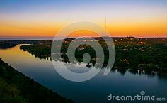 Mount Bonnell West Austin Sunrise Belt of Venus colors the sky as the sun rises over the horizon. The Colorado river bend down below is perfectly still , calm waters that show off the amazing landscape of central texas.