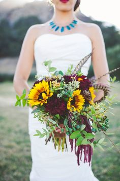A jewel tone wedding bouquet with sunflowers, dahlias, greenery, and feathers for a modern bride.