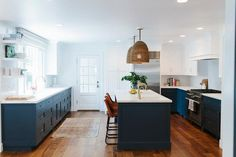 Fabulous kitchen features white upper cabinets and navy lower cabinets painted Benjamin Moore Hale Navy paired with calacatta marble countertops.