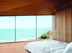 The couple, both surfers and beach lovers, wake up to stunning views of the azure-blue Southern Ocean in their otherwise monochromatic eucalyptus master bedroom. Wardle's firm designed the bed base, and the panel in the ceiling hides a television.  Photo by: Sean FennessyCourtesy of: Sean Fennessy