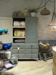 anthropologie creative store displays - layer tables and use cabinets for display.