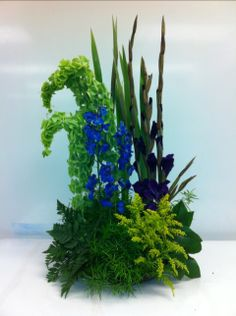 1.) Vegetative Design High - Low Shape Bells of Ireland, Delphinium, Leather Leaf, Solidago, Gladiolus, Lemon Leaf, Sprengi fern