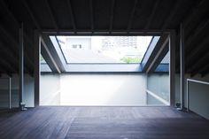"""Do segundo pavimento, é visível a estrutura aberta do átrio central, que parte de uma cobertura envidraçada e inclinada. Uma espécie de """"claraboia gigante"""". Para evitar quedas, foram usados os fechamentos em vidro que acabam por eliminar por completo a necessidade de luz artificial no mezanino durante o dia. Do lado oposto ao pano de vidro, uma porta-balcão dá passagem ao terraço da casa NA, assinada pelo arquiteto japonês Tsuyoshi Ando, em Tóquio"""