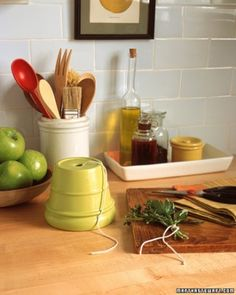 Martha Stewart  Flowerpot String Dispenser  Bring a favorite flowerpot indoors, turn it upside down, and you have a charming way to keep your kitchen string neat and accessible.  Choose a clean pot with a bright glaze, and place it over the ball of twine, threading the end through the drainage hole. Pull out the string and snip lengths for tying herb bouquets or trussing a chicken. Try this idea with wayward balls of twine and cord in your crafts closet, too.