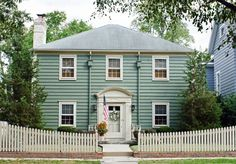 two story home with curved front yard picket fence