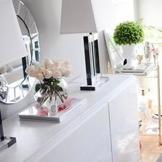Living room essentials are a decorative mirror, a sideboard, bar cart, lamps and beautiful fresh roses!!!
