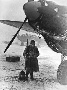 Sentry and his dog at an airfield next to German bomber Heinkel He-111 H-6 in Russia 1943.