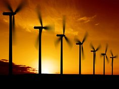 Photo is a silhouette of seven wind turbines.