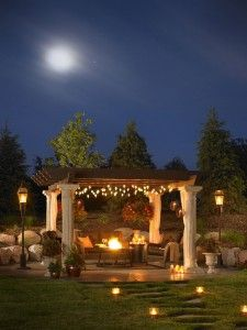 i love this idea!! an outside living room around a firepit, with closable curtains, twinkle lights, and a trellace roof!! hmm... there's gotta be a way to close that roof, too...