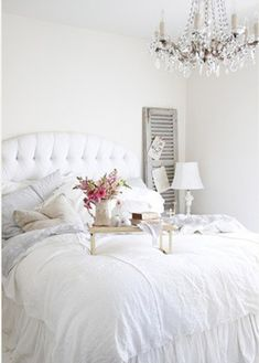 Crisp, clean and bright: the romantic white on white #bedroom with tufted headboard and chandelier