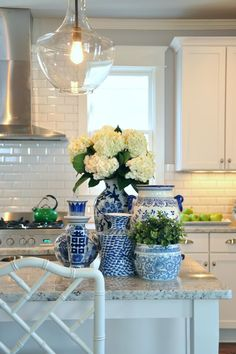 Add color and light to your kitchen with pendants and decorative vases on the island. This island, by designers Cate Dunning and Lathem Gordon of GordonDunning, uses hydrangeas and greenery in blue and white china vases to add color to the mostly white kitchen. The greenery on the island accentuates the small pops of green in the background, while the Kichler Everly Pendant creates a spotlight for the arrangement.