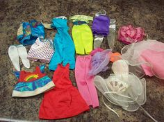 I recently picked up a large lot of vintage Barbie (and other) fashion dolls, clothing and accessories at an estate sale. All have been played with and have been stored for many years. Some items will need to be cleaned; they are sold as is.  In this lot:  2 one piece jumpsuits short wedding / party dress and fan 2 piece pants/ top 4 piece jacket, leggings and top. I think this might be one of the Rock Star outfits. tulle skirt/ top red dress 5 odd pieces (pants, top, 2 undies,...