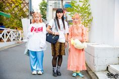 While walking around the streets in Harajuku, we met this group of 20-year-old students named Kariko, Honokappi and Otowa. At the right, Kariko with her peach and yellow twin tails is wearing a resale fashion style which features a resale peach gingham dress, yellow socks and turquoise baby doll shoes from Candy Stripper. Her accessories include a Pompompurin plushie bag which she bought online, yellow scrunchies, silver and colorful ear studs, ball chain necklace, colorful rings – some of…