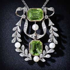 Antique Peridot, Diamond and Pearl Necklace. A unique and alluring Edwardian necklace, circa 1900, showcasing a glistening pair of lime green emerald-cut peridots, one of which surmounts, and one of which dangles from a twinkling platinum and rose-cut diamond wreath enlivened with four lustrous natural pearls. This wonderful and ravishing antique jewel measures 1 5/16 inch by 1 1/8 inch. The white gold chain from Italy is new. Lang Antiques.